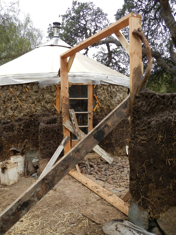 The door buck is braced from inside and outside to keep it level, while the cob walls set. We'll keep it in as long as we can. Clay shrinks as it dries, and it is expected that the cob walls will shrink a couple of inches and can potentially twist the door buck out of alignment.