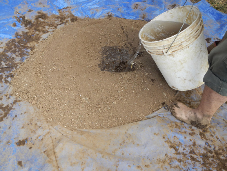Our cob recipe is 1 part local soil, 1 part sand and 1/4 part clay (high-clay soil). We place it all on the tarp and gradually add water.