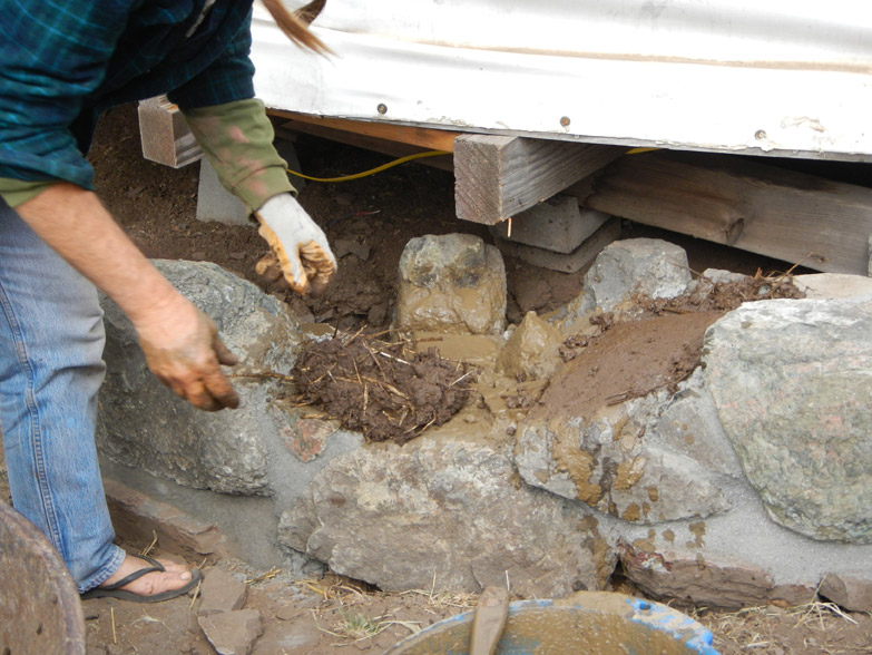 Then we apply cob directly to the stone foundation to begin the wall!
