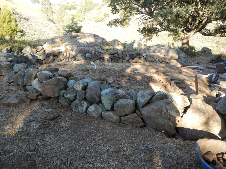 Step 4 - dry stacking serpentine stone, collected from surrounding hills, to create the base for the walls